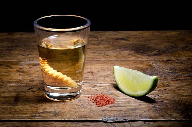 chupito de tequila con lima y sal sobre fondo vintage. - mezcal fotografías e imágenes de stock