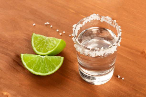 un tequila con lima selices sobre un fondo de madera rústico con copyspace - mezcal fotografías e imágenes de stock