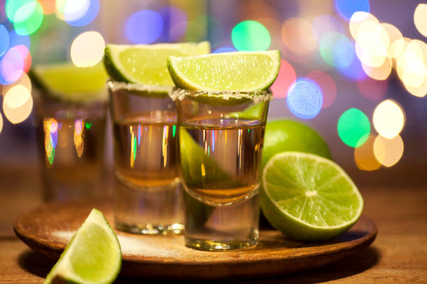 Tequila shots on a bar Gold tequila shots with lime fruits on wooden table on bar lights background tequila shot stock pictures, royalty-free photos & images