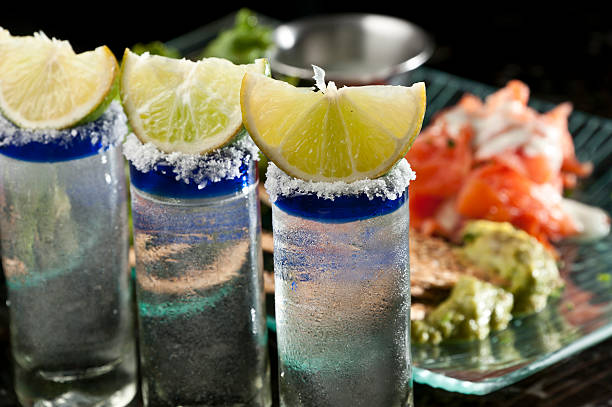 Tequila shots Three tequila shots and a Mexican appetizer in the background tequila shot stock pictures, royalty-free photos & images