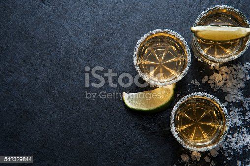 istock Tequila shots with lime slice, top view 542329844