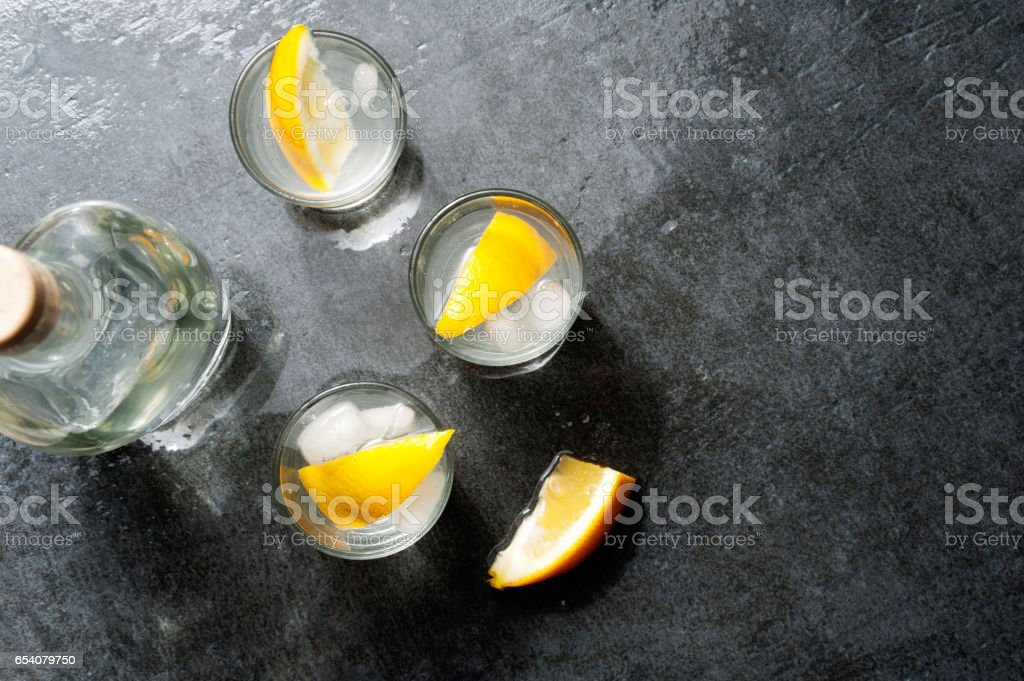 Tequila vodka shots with lemon slices, top view stock photo