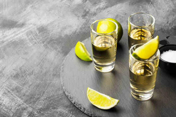 Tequila with lime and salt on a dark background. Copy space. Food background Tequila with lime and salt on a dark background. Copy space. Food background tequila shot stock pictures, royalty-free photos & images