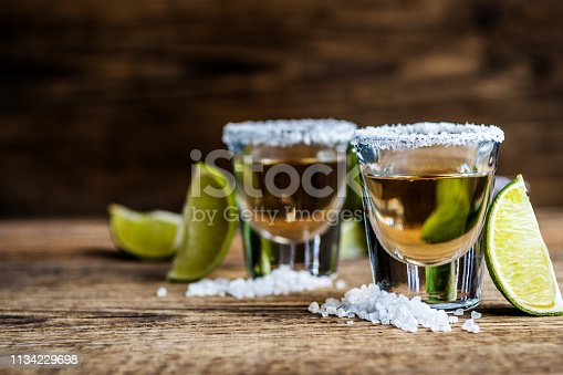 Mexican traditional alcohol drink Tequila with lime and salt and ice cube on wood table