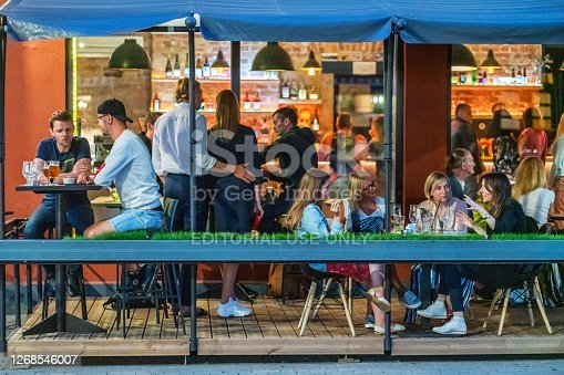 Riga, Latvia - July 17, 2020: People sitting by tables at an outdoor cafe.