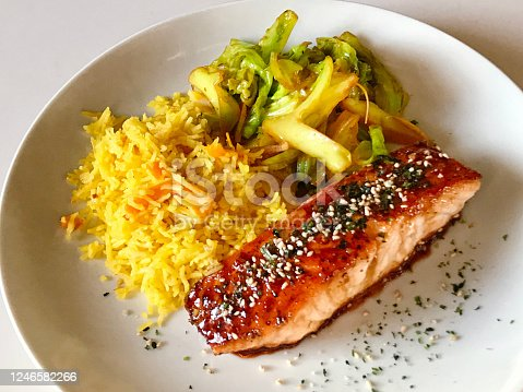 An entree of teriyaki glazed salmon fillet served with saffron rice and sauté Napa cabbage vegetable.