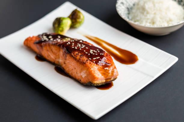saumon teriyaki sur fond noir. - glaçage photos et images de collection
