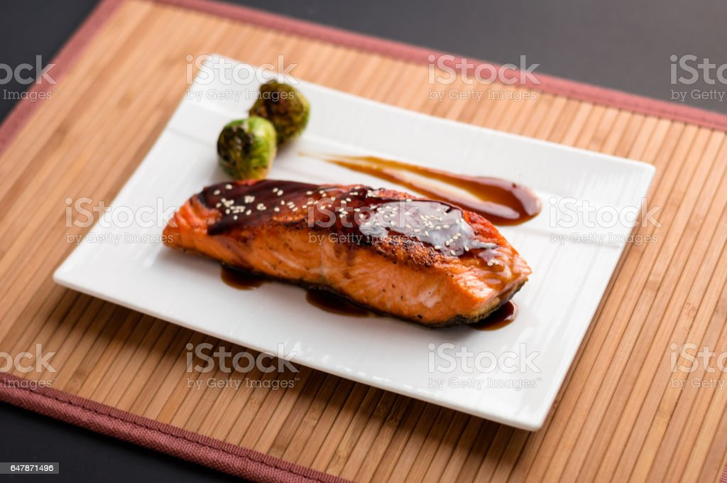 Teriyaki salmon plate on bamboo mat. stock photo