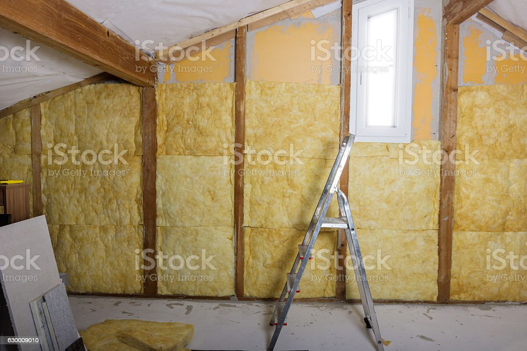 termal insulation installing at the attic with metallic ladder stock photo