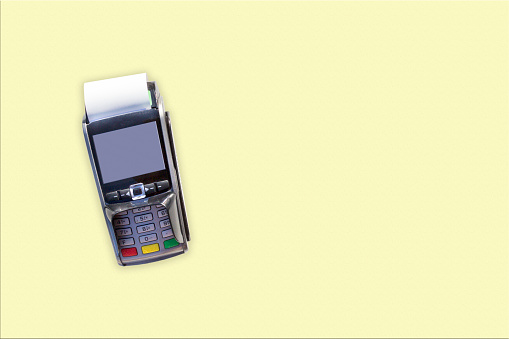 POS terminals, hand swiping credit card, payment with NFC tecnology isolated on light yellow background