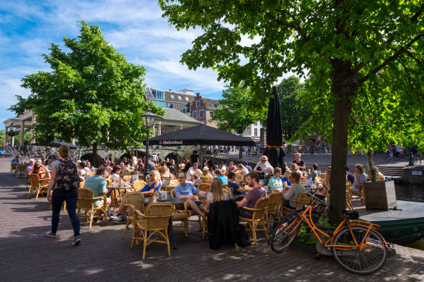 Terrace of a bar in Leiden Dozens of people enjoy a snack on a terrace of a bar in the historic center of Leiden. leiden stock pictures, royalty-free photos & images