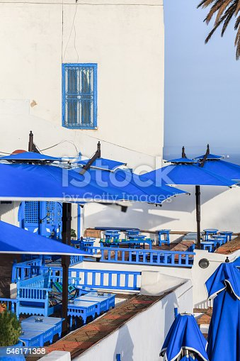 Terrace of oriental style restaurant with blue wooden tables and benches