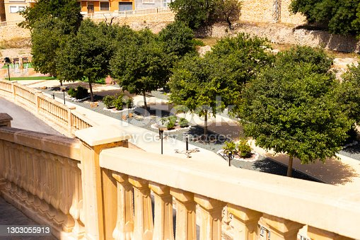 Terrace with balustrade and beautiful views of the park with fruit trees and a sports complex on the street on a sunny summer day