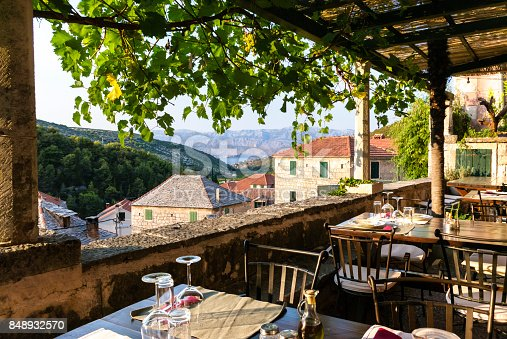 Terrace with tables and chairs with beautiful views of the town, sea and mountains. Dol - small town on Brac Island, Dalmatia, Croatia. Tourism.
