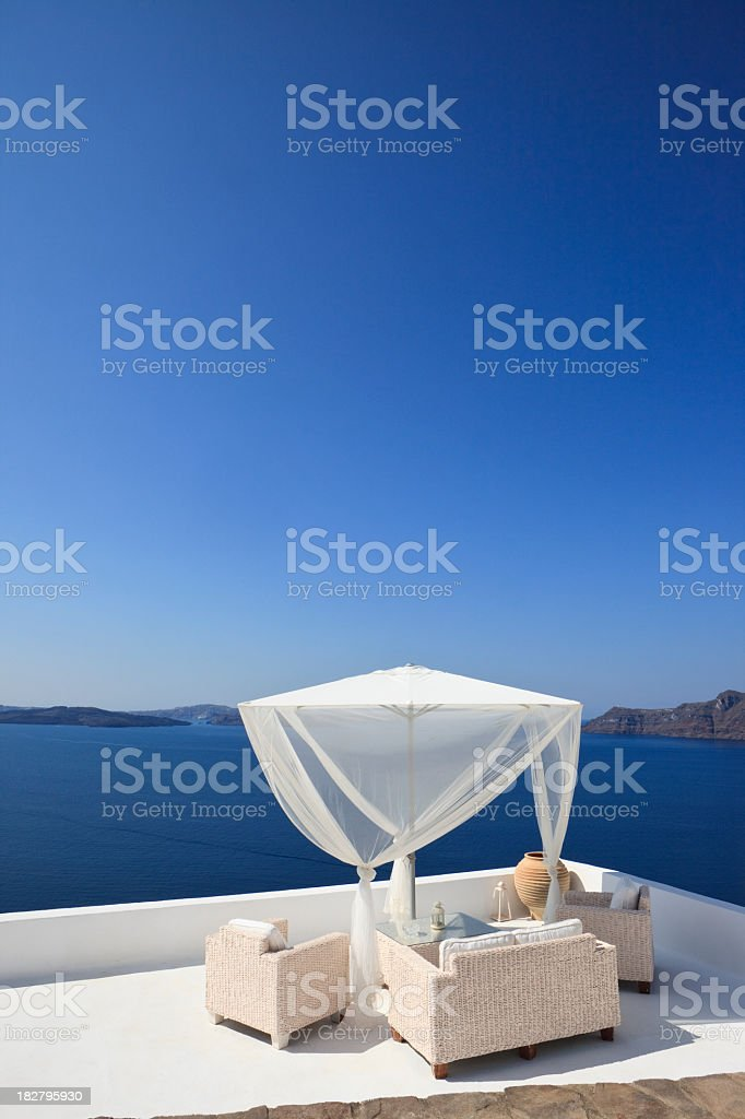 Terrace with seating furniture and parasol in Oia, Santorini royalty-free stock photo