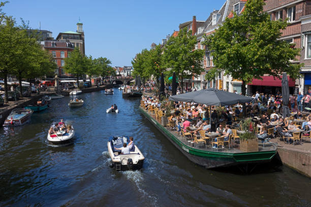 Terraces and boats near the canal called Nieuwe Rijn, in summer Leiden, Netherlands - May 20, 2018: Terraces and boats near the canal called Nieuwe Rijn, in summer leiden stock pictures, royalty-free photos & images