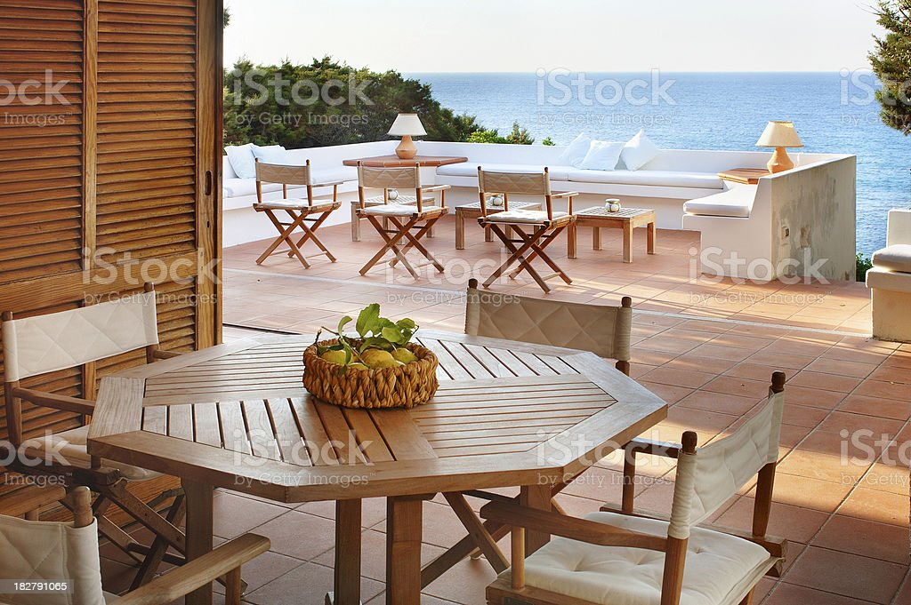 Terracotta terrace with wooden furniture of a beautiful seaside house royalty-free stock photo