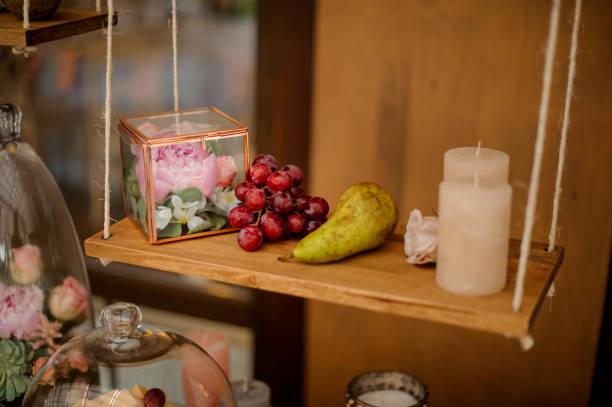 terrarium mit einer pfingstrose blume, trauben, birnen und kerze - jasmin party stock-fotos und bilder