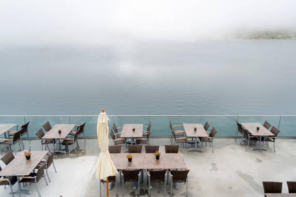 terrasse mit tischen am seeufer, nebel, passhöhe grimsel, schweiz - hotel bern stock-fotos und bilder