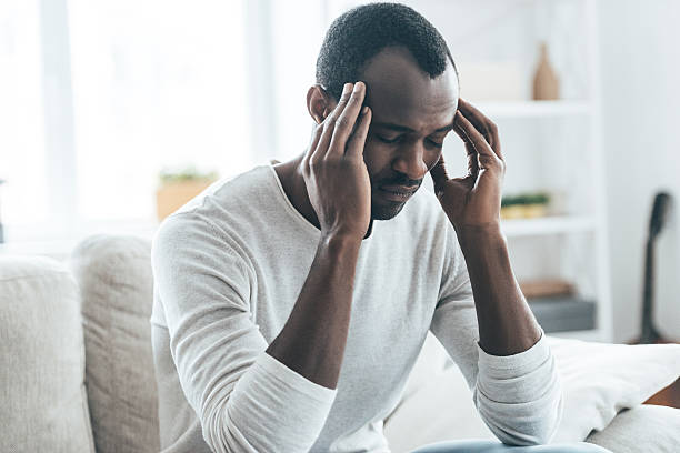 Terrible headache. Young African man touching head with hands and keeping eyes closed while sitting on the sofa at home headache stock pictures, royalty-free photos & images