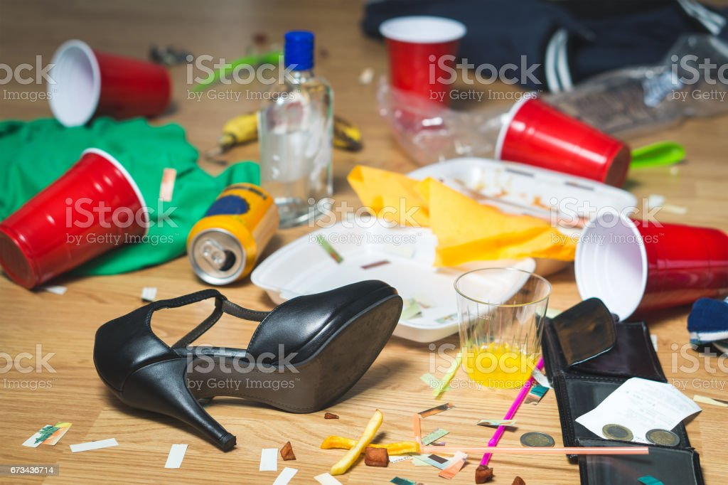 Terrible mess after party. Trash, bottles, food, cups and clothes on the floor. Messy apartment after guests leaving or the next morning. Horrible chaos after crazy wild night. stock photo