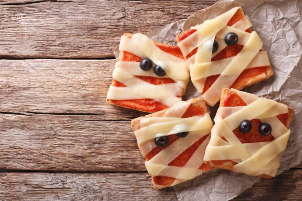 schreckliche sandwiches für halloween in form einer mumie. horizontale ansicht von oben - halloween party lebensmittel stock-fotos und bilder