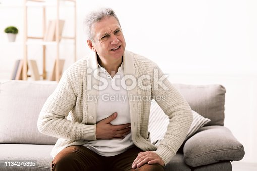 Terrible stomachache. Senior man hugging his belly, suffering from pain at home