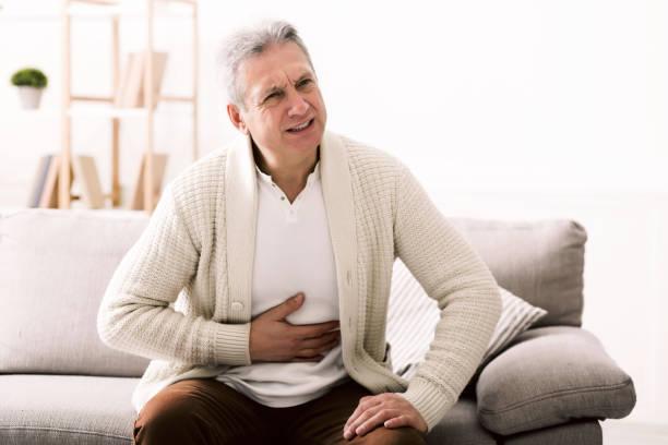 terrível dor de estômago. homem sênior que abraça sua barriga, sofrendo da dor - sistema digestivo humano - fotografias e filmes do acervo