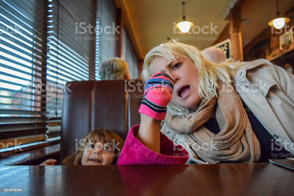 Terrible table manners Little girl puts her socked foot on the table at a restaurant, her mother looks on in horror 2-3 Years Stock Photo