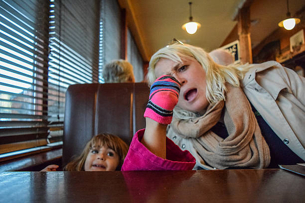 Terrible table manners Little girl puts her socked foot on the table at a restaurant, her mother looks on in horror prettige verrassingen stock pictures, royalty-free photos & images