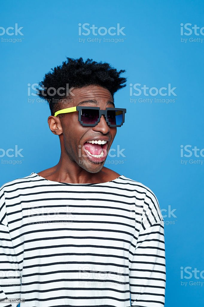 Terrified afro american guy wearing sunglasses Terrified afro american young man wearing striped top and sunglasses, shouting. Studio portrait, blue background. Adult Stock Photo