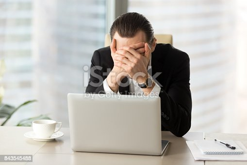Terrified businessman covering face with hands in front of laptop. Distressed CEO shielding himself from disastrous financial result. Received terrible news, business failure, enormous debt concept.