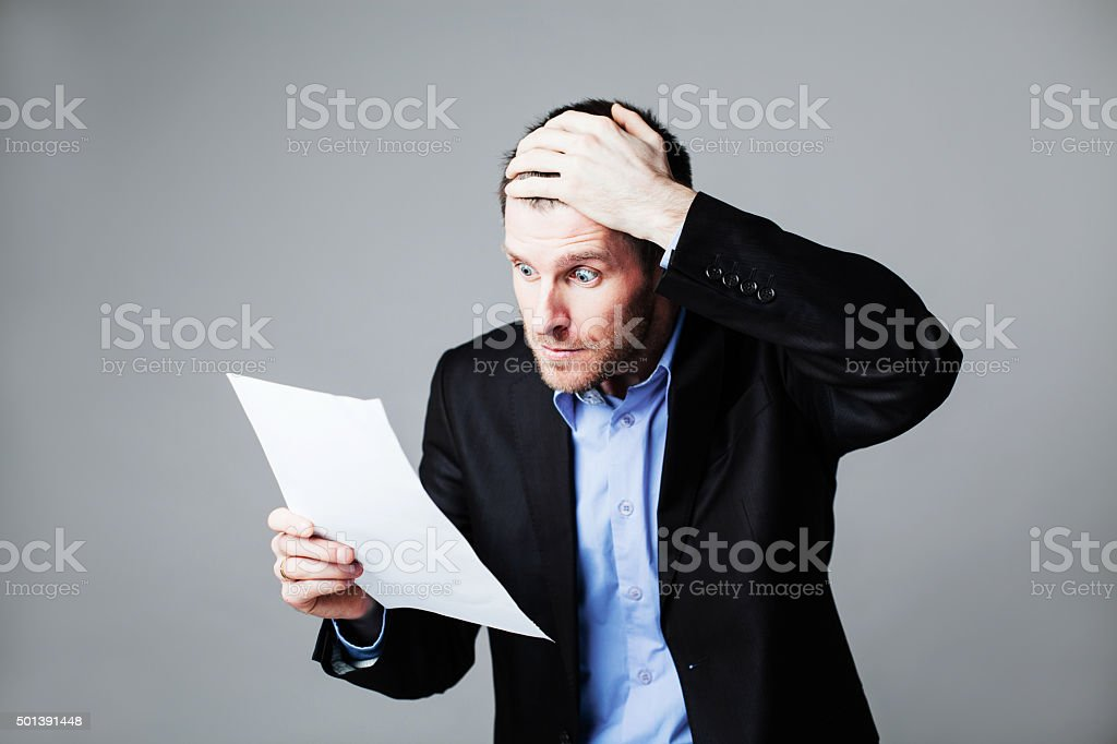 terrified businessman reading document stock photo