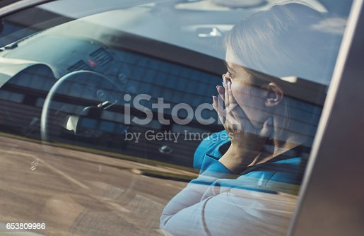 Businesswoman sitting in the car and covering her mouth in shock. The view is through glass.