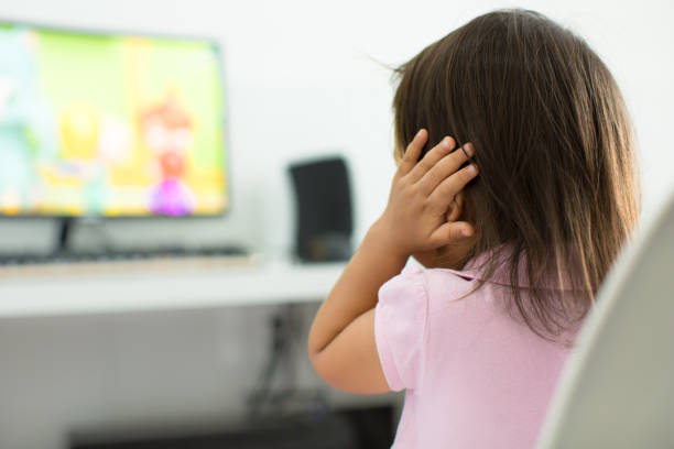 A terrified child, afraid of the loud sounds from the television. Autism. A child watching tv holding her ears because she is afraid of the sound; Child behavior theme autism stock pictures, royalty-free photos & images
