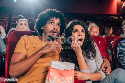 Scared young people at cinema together