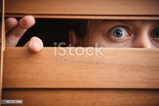 A young woman peers nervously through a wooden venetian blind.