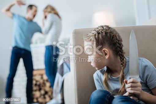 istock Terrified little girl holding a knife 909407892