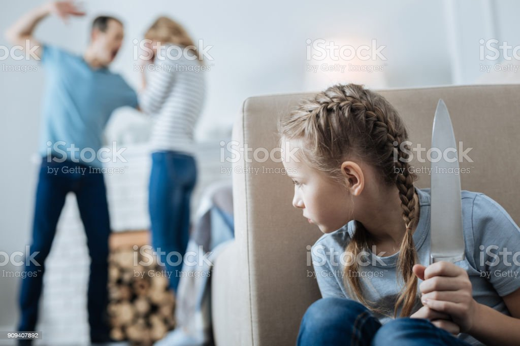 Terrified little girl holding a knife stock photo
