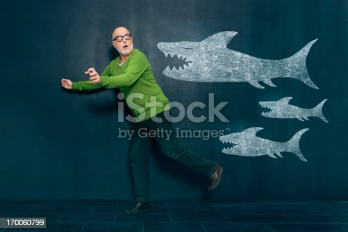 istock Terrified man escaping from sharks 170060799