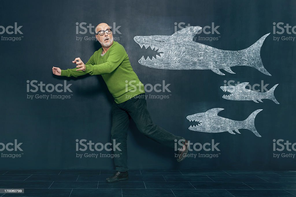 Terrified man escaping from sharks stock photo