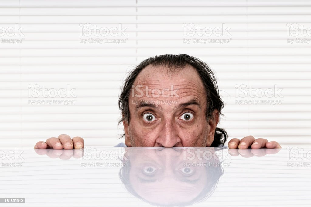 Terrified Man Looking over the Table stock photo