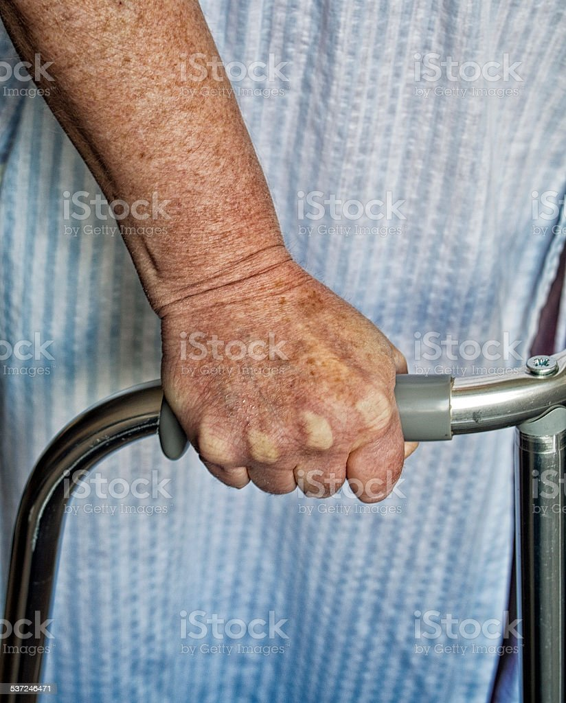 Terrified old lady holding on to a walking frame stock photo