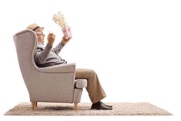 Terrified senior with a popcorn box and 3D glasses seated in an armchair stock photo