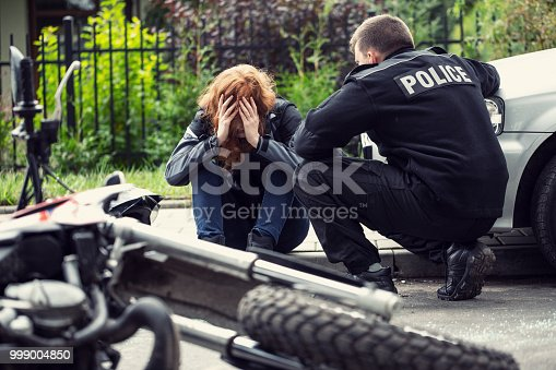 istock Terrified victim of a traffic collision of motorcycle with a car and policeman 999004850