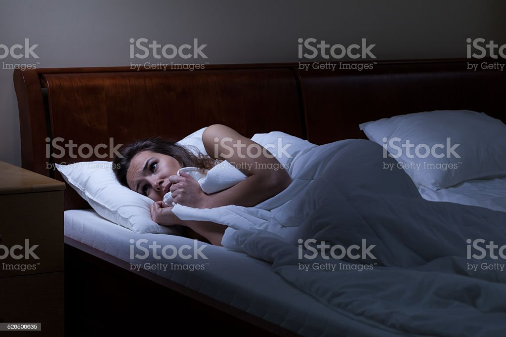 Terrified woman lying in bed stock photo