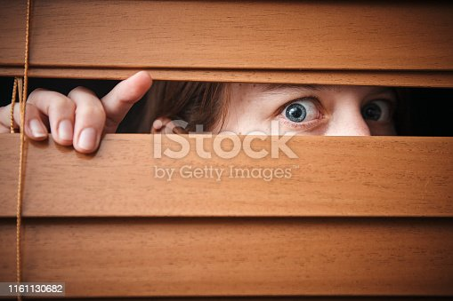 Wide eyed and scared, a young woman peeks nervously through a wooden blind.