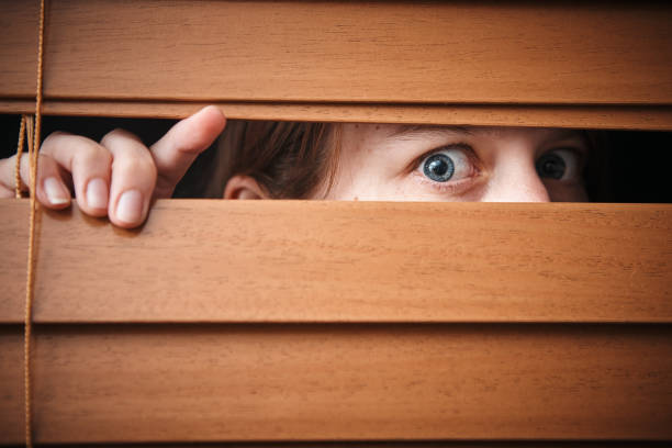Terrified young woman peeps through wooden venetian blind stock photo