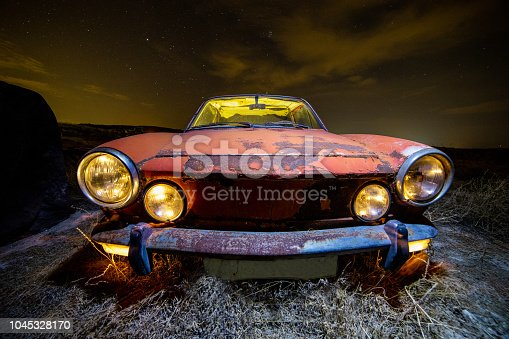 Ancient car abandoned in the countryside and illuminated with lanterns