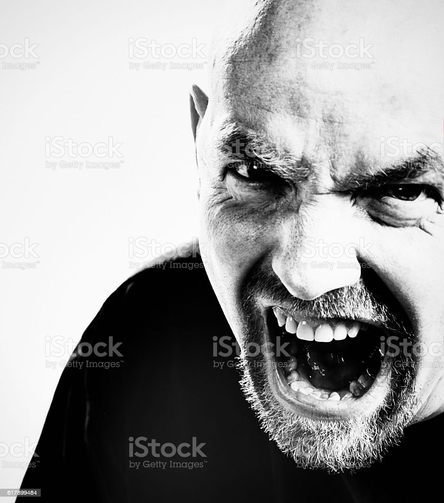 Terrifying man threatens, grimacing and yelling stock photo